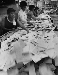 Photograph showing black women postal clerks sorting mail in the Chicago Post Office circa 1970.