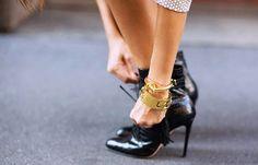 Braceletes dourados e ankle boot preta.