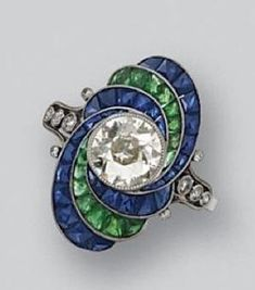 DIAMOND, SAPPHIRE AND EMERALD RING, CIRCA 1925. Set with an old European-cut diamond weighing approximately 1.00 carat within an oval frame decorated with swirls of French calibré-cut emeralds and sapphires, the shoulders accented with small old European-cut diamonds, mounted in platinum by amelia