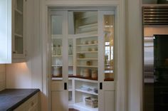 source: Giannetti Home Glass pocket doors into butler's pantry! White kitchen cabinets, soapstone counter tops, built-in shelves, glass front cabinets, oil-rubbed bronze door hardware and white paint wall color. Glass Pantry Door, Glass Front Cabinets, Pantry Doors, White Cabinets, Built In Shelves, Open Shelving, Glass Shelves, Custom Shelving, Glass Pocket Doors