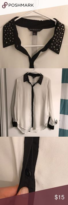 Rock & Republic Blouse White slightly sheer blouse with black collar, trim, and cuffs. Studded collar. Two stud buttons on each sleeve near cuff. Black plastic buttons down front covered by black fabric. Small stain on back (pictured), otherwise in great condition. Rock & Republic Tops Button Down Shirts
