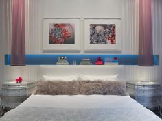 In this elegant modern bedroom, a horizontal nook with cool blue lighting stores books and accessories behind the bed. Two beautiful silver nightstands pair with long, pink striped pendant lights, and framed matte art brings in a light shade of red to complement the pink accessories. Faux fur pillows and white linens complete the chic design.