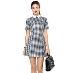 """Motel Joni Dress This black and white checkered skater dress will take you through graduations, summer parties and nights out! It features a white collar, fitted waist and short sleeves. Zip/hook closure at back, unlined. Toughen it up with a moto jacket! By Motel.  *100% Viscose  *31""""/79cm bust  *28.5""""/72.5 cm waist  *32""""/81cm length  *Model is wearing size small  *Measurements taken from size small  *Hand wash cold  *Imported Nasty Gal Dresses"""