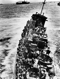 A Coast Guard ship badly damaged in the D-Day attack, transporting its troops to safety before sinking, June 6, 1944. U.S. Coast Guard photograph.