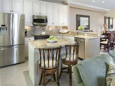 White condo kitchen with granite, stainless appliances and center island seating.  Broadview Villas on 6th Street South in Olde Naples, Florida