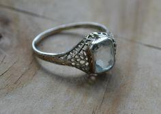 Beautiful edwardian / early art deco 14k white gold filigree engagement ring with aquamarine blue gem. $199.99, via Etsy.