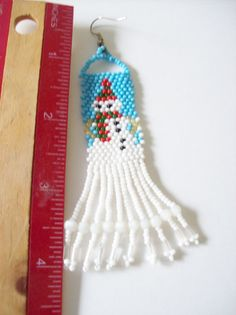 Beadwork Dangle Earrings , Beaded Snowman Earrings , Handmade Christmas Earrings , Holiday Earrings , Seed Bead Earrings A pair of beaded snowman earrings is handmade my me. In making the earrings I used a 6 lb beading thread and a size 11/0 seed beads in a blue , red , green , black , gold and white. The earrings are 4 inches long from the top of the silver plated ear wires to the bottom of the fringe, these are also light weight to wear. To view my other items in my shop, please click on…