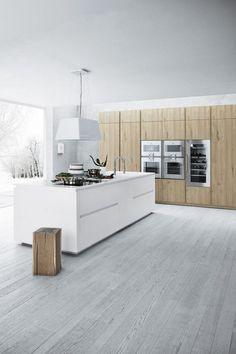 îlot de cuisine moderne avec sol en parquet gris clair, meubles en bois massif et hotte design assortie