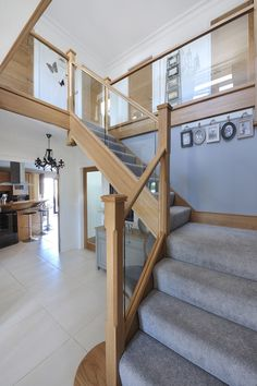 We used a modern mix of glass and natural oak with carpeted treads that sweep around the first-floor landing. This allowed us to create a contemporary style staircase with half landing. To add to the modern finish, glass is inset into the wooden staircase frame for a streamlined look. An alternative to using more traditional spindles.