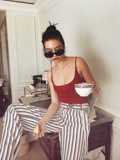 Red spaghetti strap bodysuit paired with high waisted, black and white striped trousers.