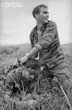 """28 Jun 1969, Ben Het, South Vietnam --- June 28, 1969 - Ben Het, South Vietnam: A GI applies a makeshift bandage to the head of a wounded buddy while keeping an eye out for the enemy during fighting """"outside the wire"""" of U.S. Special Forces camp at Ben Het."""