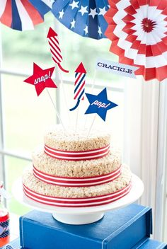 "Want an EASY 4th of July ""Cake?""?  Ready in 30 minutes or less!  RICE Krispie Treat Cake with red white and blue cake printable toppers saying ""Snap, crackle, pop"" and fireworks! Get it!?"