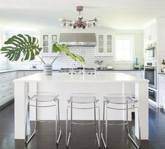 Stunning monochromatic white kitchen features three clear acrylic island stools placed on dark stained oak floors in front of a white kitchen island fitted with legs and a white quartz countertop lit by a modern bulb chandelier.