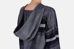 Lemlem is designer and model Liya Kebede's collection of luxuriously rustic womenswear, handwoven in her native Ethiopia. This relaxed pullover, in fine merino wool blended with cotton, combines broad horizontal stripes with a gradient of greys. Designed to hit at the hip, the drop-shouldered silhouette has a notched neckline and a slit hem. Its easy fit, deep cloak hood, and neutral palette make it an especially adaptable coverup.