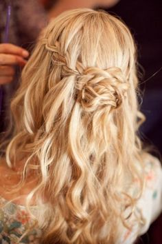 half up hairstyle with liberated waves of hair on the bottom and an intricate plait around the crown that comes together from both sides to form a more ample braid near the center of the back of the head