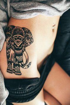Um elefante coberto em um padrão de mandala é processado em tinta preta sobre o portador do quadril neste tatuagem.