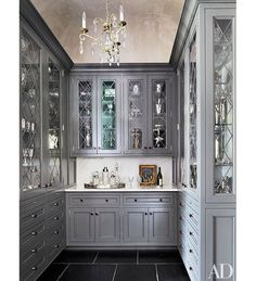 At a South Carolina home designed by Barbara Westbrook, diamond-pattern glass door fronts and a crystal chandelier lend a dressed-up look to the cabinetry in the butler's pantry.