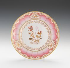 """A KPM Porcelain Plate From the """"Damaskus"""" Service Marked on the underside with the blue scepter in underglaze, iron red orb and KPM, 1903 in blue, Prussian Royal crown above in blue for Emperor Wilhelm II, and impressed characters. Painted in the Chinese taste in puce, sepia, iron red and gilt with flowering plants in the center enclosed in a meandering border, with a lotus petal around the rim with three foliate reserves, the lip with foliate designs within a gilt rim."""