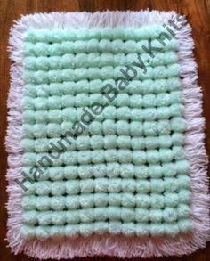 Mint pom pom blanket with white base and tassles.