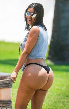 Kimoj-eez! Kim displayed her sizable behind in a thong bikini on Sunday after unairbrushed...