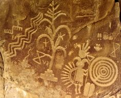 Pre-contact petroglyphs at Largo Canyon, NM. [Depicts a corn plant, mythical figure and various other petroglyphs. Crow Canyon. Navajo people interpret this as a representation of Gháá' ask'idii. His horns tie him to the Mountain Sheep People, an ancient race associated with the night chant, Tl'eejí. Generally a benevolent figure, Gháá' ask'idii carries many kinds of seeds and foods in his feather-crowned backpack.Some recent graffiti vandalism is apparent on closer inspection. JE]