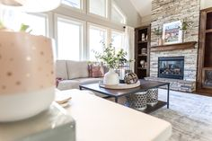 Gorgeous blush living room with stone fireplace and off-white sectional.