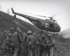 """""""Return flight-An GRS-1 Sikorsky transport helicopter lifts away with a load of casualties after disembarking the Marines in foreground."""""""