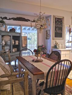 Farmhouse Kitchen - this dining area, with its vintage lighting and furnishings, has tons of charm - via Chateau Chic