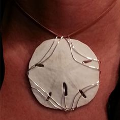 "Hand picked sand dollar carefully wrapped with sterling silver is a stunning statement piece. Comes with a 18"" sterling silver box chain. $ 150.00"