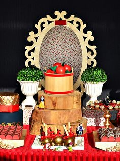 Pretty red and gold Snow White Themed Dessert Table with gold candy apples, glittery crown cupcake toppers, apple cake pops and a rustic wooden centerpiece!