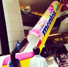 Mentos made a huge slide so kids can act like they are a mentos that slides out of the packaging while their moms are shopping #AllAboutMarketing