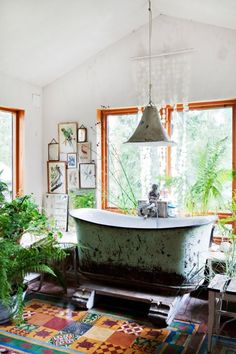 Vintage bath in a Norwegian cabin - colorful floor tiles (turtles!), an enormous beaten bathtub, bird etchings on the walls, shell panel curtain, & house plants #bohemian #interior