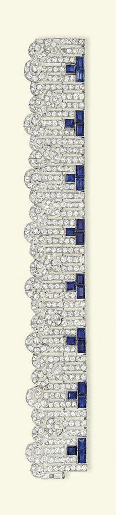 AN ART DECO SAPPHIRE & DIAMOND BRACELET   Designed as a series of brilliant-cut diamond baton links with scrolling terminals & rectangular-shaped sapphire three-stone accents, ca 1930, 19.2 cm long.