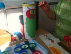 """Very Hungry Caterpillar.  """"Simply cover a Pringles tin with some plain paper, stick and cut out (or print out of the caterpillar on to the tin- and cut out a slot for the mouth big enough to post milk bottle caps in. Stick pictures of each of the food items onto milk caps"""""""