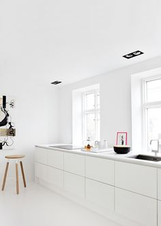 white kitchen clean lines space minimalist styling design windows white flooring, cabinetry and walls