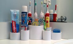 DIY: Toothbrush/paste holder for a family of 6! Various sizes of PVC pipes hot glued together.