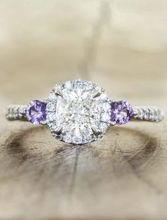 I wouldn't want a stone this huge and I also am not fond of the cut, but I'm pinning this because I never thought about putting colored stones on an engagement/wedding ring. Purple is my favorite color and these purple sapphires are absolutely beautiful with the diamond!