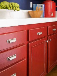 Another budget-friendly approach to kitchen remodeling is painting the existing cabinets. These homeowners gave their rich red paint an aged look by roughing up the edges with sandpaper. Modern stainless-steel pulls complete the new look.