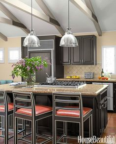 """""""To give the kitchen a facelift without breaking the bank,"""" Leverone says, the rafters were painted in Benjamin Moore Aura in Plymouth Rock, with dark accents to match the repainted cabinetry."""
