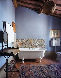 Lilac walls, ceramic tiles, claw foot, rug on floor, antique makeup/dressing table.
