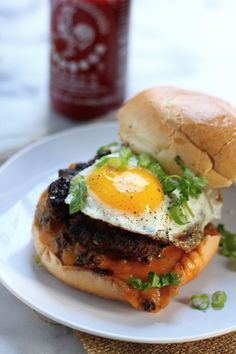 """Sriracha and Cheddar """"Jucy Lucy"""" Burgers - Classic burgers get spiced up with sriracha, stuffed with cheddar cheese, and topped with an egg!"""