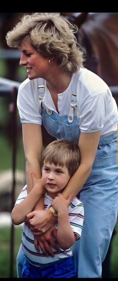 June 28, 1987: Princess Diana here with Prince William at Smiths Lawn, Windsor. Princess Diana wears pale blue denim dungarees with a rope style belt, and white blouse top.