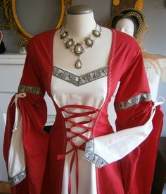 This awesome dress is perfect for a stroll over the medieval market or ren faire, it would also be perfect as a wedding dress, or for the bridesmaids. It is made out of cotton in red and natural white(not bleached white). It has extra long overs sleeves which are tied up, the under sleeves in white are narrow and pointed at the wrist and the dress has side seams insets in white.The dress has a corset type lacing in front and back for a perfect fit without cinching or bursting out of the…