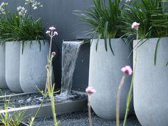 Smalle spiegelvijver met een subtiele wateruitloop uit de muur. Zo creëert u leven in de tuin en voorkomt u veel onderhoud aan een vijver.
