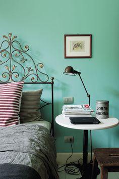 Une tête de lit travaillée en fer tranche avec le mur vert d'eau dans la chambre.