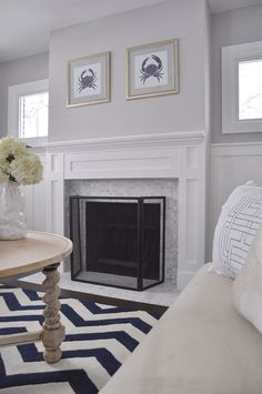 Benjamin Moore Stonington Gray with a marble fireplace surround with white mantel and wainscoting in a living room by Lindsay and Drew