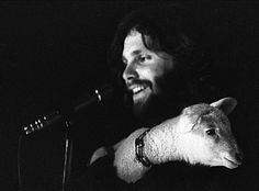 Jim Morrison. On stage during Miami infamous concert. The lamb was brought to the concert by Jim's friend who was traveling with it to spread vegan awareness. Jim remarked, even though the room was chaos, the lamb was calm & relaxed in his arms. :)