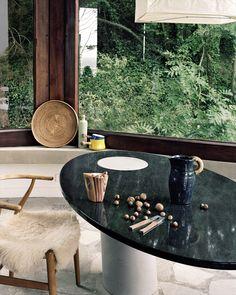 Une maison seventies a Dinard Dans l'espace cuisine de la maison, la table de la série Eccentrico d'Angelo Mangiarotti (Galerie Yves Gastou) affiche son marbre noir et la chaise vintage Wishbone de Hans Wegner, son mouton blanc. Les céramiques vintage ont été chinées.