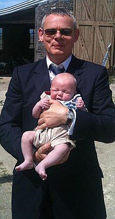 Martin Clunes holding one of the several babies that play James Henry Ellingham on Doc Martin.