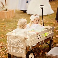 """The two flower girls were pulled in a hand-painted wagon by Ariel's 12 year old nephew, who, according to the bride, """"wore his shades the entire time...ultra cool!"""" Guests were told that the bride was coming next by the sign on the back of the wagon. Photo Credit: Bellagala"""